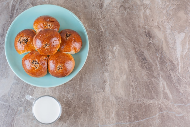Domowe ciasteczka z mlekiem na niebieskim talerzu na szaro.