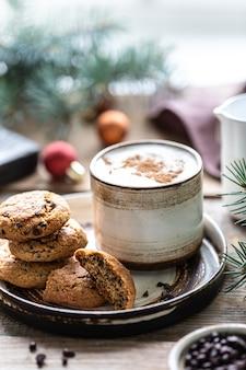 Domowe ciasteczka z orzechami i kawą w ceramicznym kubku na drewnianym stole z zabawkami i gałęziami choinki.