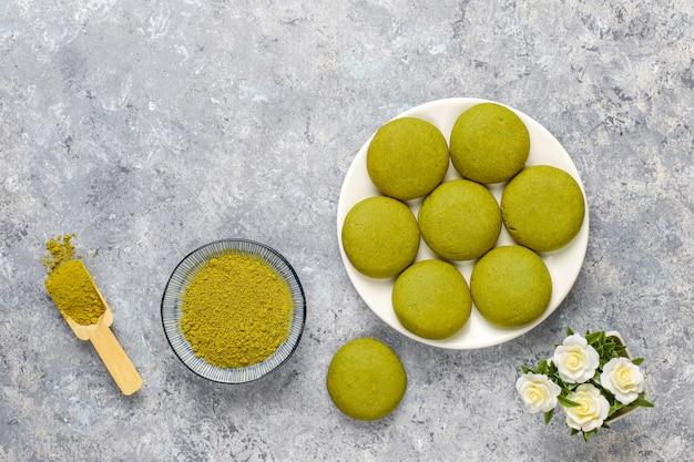Domowe ciasteczka z zielonej herbaty matcha z proszkiem matcha na szarym betonie