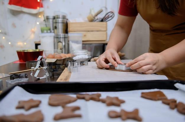 Domowe ciastko świąteczne na boże narodzenie i szczęśliwego nowego roku. kobieta gotowania piernika z przyjacielem i rodziną na ferie zimowe w domu.