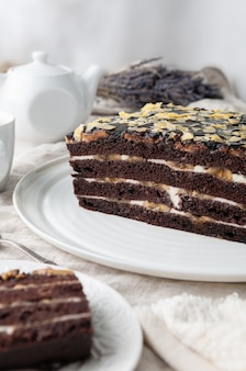 Domowe ciasto bananowe. z ciastem biszkoptowo-czekoladowym. nasączony kremem maślanym. doprawione czekoladą. na białym talerzu. w tle dawny czajniczek i kubek.