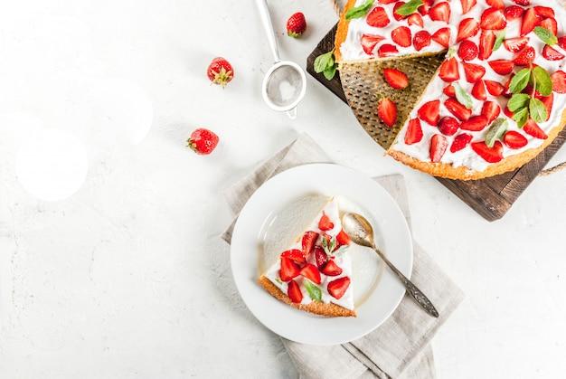 Domowe ciasto biszkoptowe z bitą śmietaną, świeżymi organicznymi surowymi truskawkami i miętą. na białym kamiennym stole. widok z góry lato