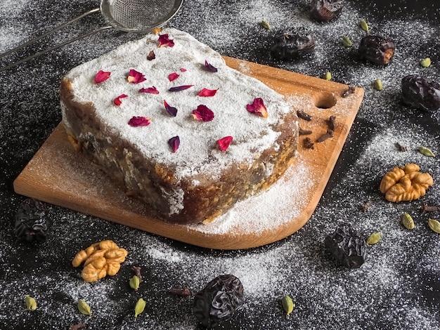 Domowe ciasto brownie z daktylami i orzechami posypane cukrem pudrem na ciemnym stole