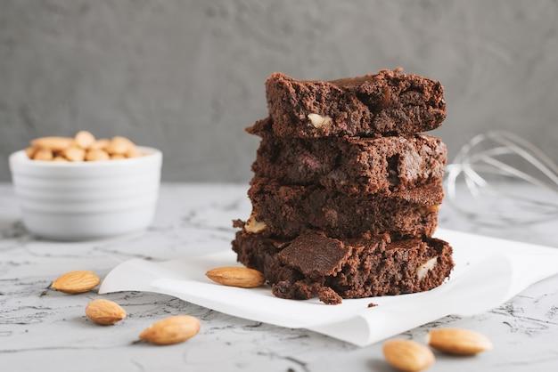 Domowe ciasto czekoladowe brownie zapiekane z orzechami migdałowymi i podawane na papierze do pieczenia
