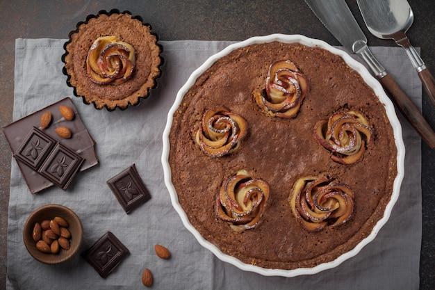 Domowe ciasto czekoladowe z kwiatami frangipanu i jabłka na ciemnej betonowej lub kamiennej powierzchni drewna. selektywna ostrość. widok z góry. skopiuj miejsce.