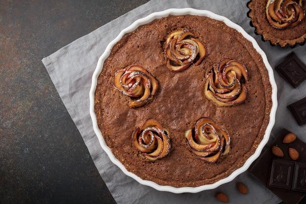 Domowe ciasto czekoladowe z kwiatami frangipanu i jabłka na ciemnym betonie