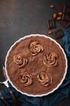 Domowe ciasto czekoladowe z kwiatami frangipanu i jabłka na ciemnym betonowym lub kamiennym tle