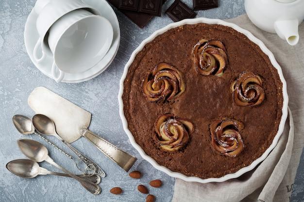 Domowe ciasto czekoladowe z kwiatami frangipanu i jabłka na jasnoszarym betonie lub kamiennej powierzchni drewna. selektywna ostrość. widok z góry. skopiuj miejsce.