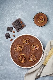Domowe ciasto czekoladowe z kwiatami frangipanu i jabłka na jasnoszarym betonie