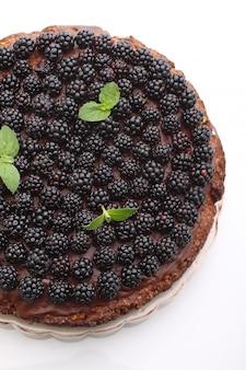 Domowe ciasto czekoladowe z orzechami i jeżyny na białym tle