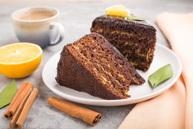 Domowe ciasto czekoladowe z pomarańczą i cynamonem z filiżanką kawy na szarym tle betonu. widok z boku, selektywne focus.