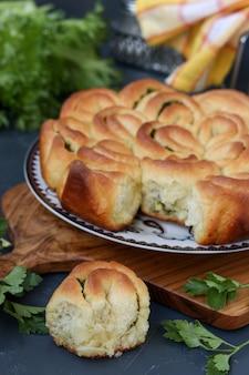 Domowe ciasto drożdżowe z ziołami i czosnkiem na ciemnym tle