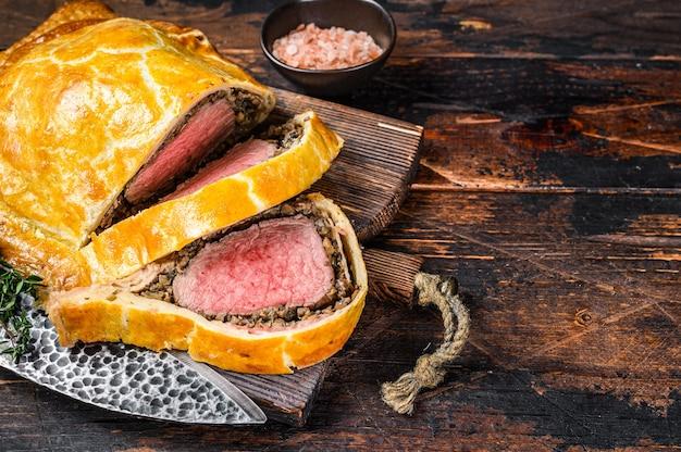 Domowe ciasto francuskie wellington z wołowiną z mięsem z polędwicy na desce do krojenia.