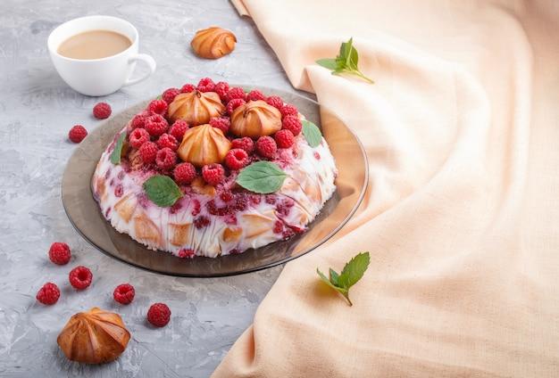 Domowe ciasto galaretkowe z mlekiem, ciastkami i malinami na szarej betonowej powierzchni z filiżanką kawy i pomarańczową tkaniną, widok z boku.
