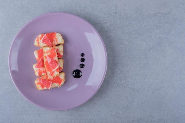 Domowe ciasto grejpfrutowe na fioletowym talerzu