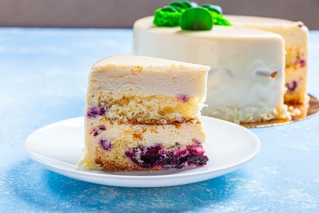 Domowe ciasto jagodowe ozdobione białym lukrem, śmietaną i świeżymi jagodami.