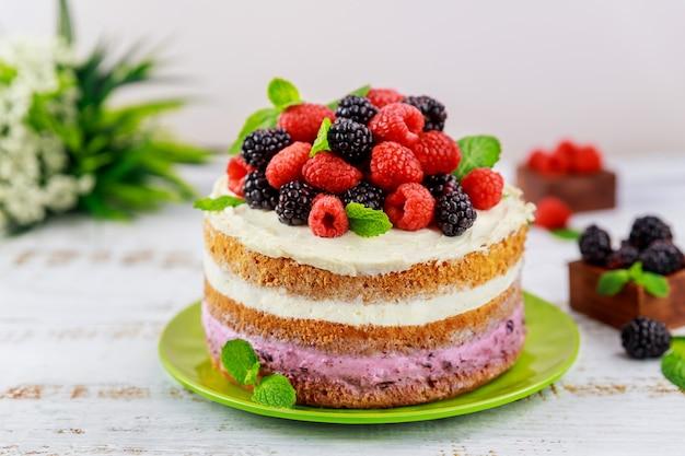 Domowe ciasto jagodowe ozdobione świeżymi malinami i jeżynami na białym tle.