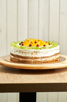 Domowe ciasto karmelowe z owocami. drewniane tło.