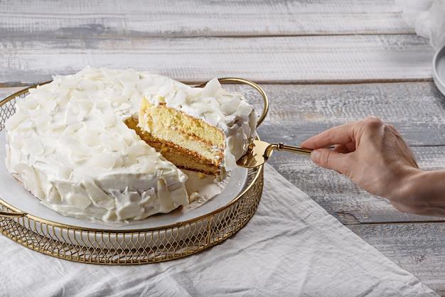 Domowe ciasto kokosowe kawałek ciasta na łopatki w ręku koncepcja domowej kuchni