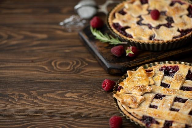 Domowe ciasto malinowe z kruchego ciasta i herbaty z hibiskusa na drewnianym stole