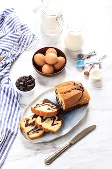 Domowe ciasto marmurowe czekoladowo-waniliowe. pokrojony z herbatą lub kawą. białe tło