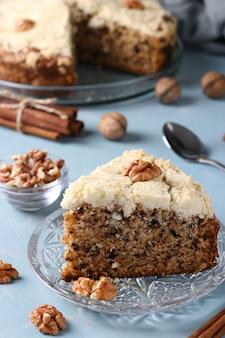 Domowe ciasto miękisz z orzechami i cynamonem w talerzu na jasnoniebieskim tle