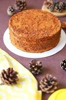 Domowe ciasto miodowe na brązowym stole z szyszkami