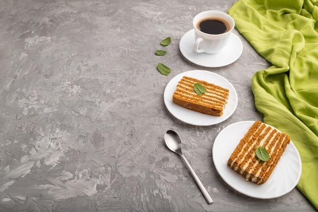 Domowe ciasto miodowe z kremem mlecznym i miętą z filiżanką kawy na szarym betonowym stole