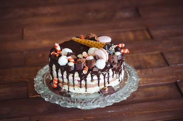 Domowe ciasto ozdobione słodyczami, makaronikiem i goframi.