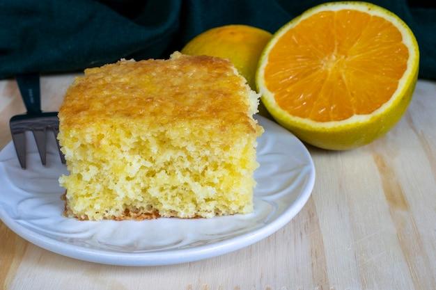 Domowe ciasto pomarańczowe na białym talerzu.