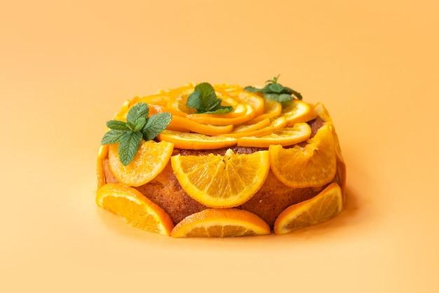 Domowe ciasto pomarańczowe z plasterkami pomarańczy na białym tle