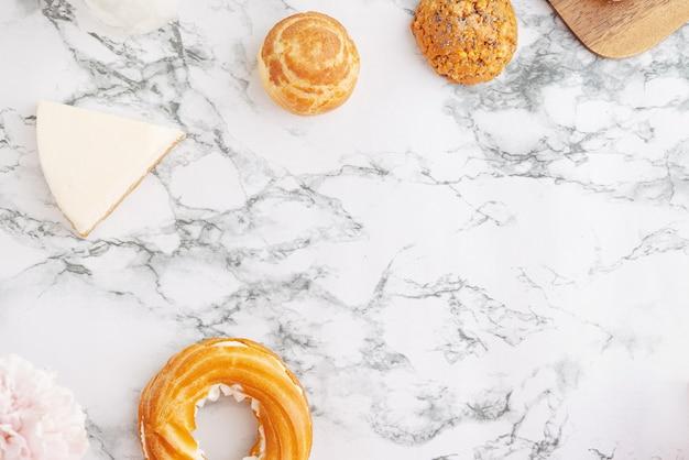 Domowe ciasto profitroles wypełnione eklerami budyniowymi z kremowym francuskim deserem i kwiatami na mar...