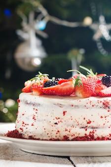 Domowe ciasto red velvet ozdobione kremem i jagodami na świątecznej powierzchni