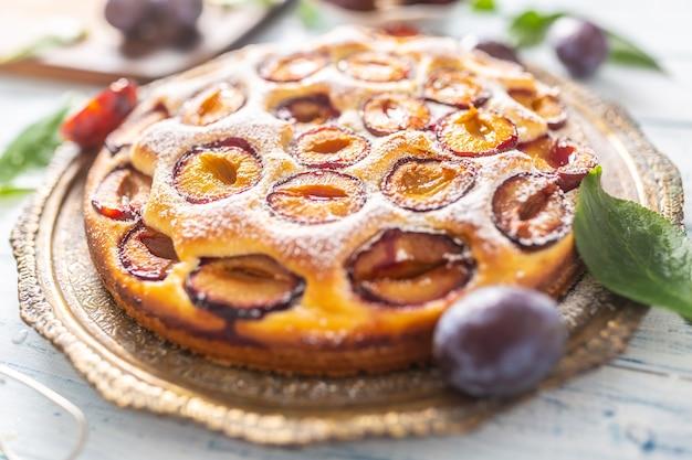 Domowe ciasto śliwkowe w vintage płyta na drewnianym stole. ciasto śliwkowe z cukrem pudrem.