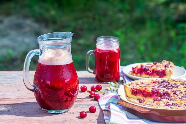 Domowe ciasto wiśniowe i czerwony napój wiśniowy na drewnianym stole w tle ogrodu, z bliska