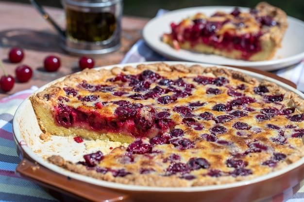 Domowe ciasto wiśniowe na drewnianym stole w ogrodzie na tle rustykalnym, z bliska