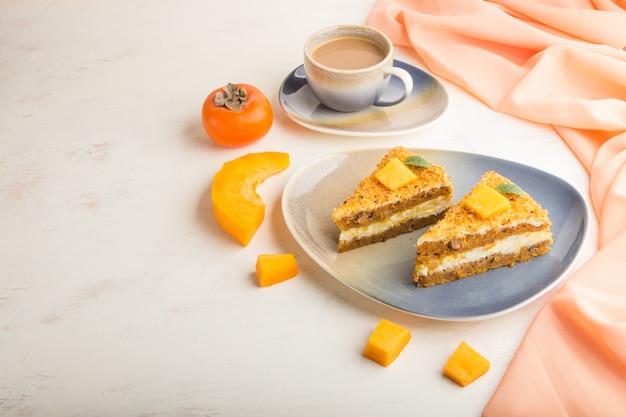 Domowe ciasto z persimmon i dyni i filiżankę kawy na białym tle drewnianych z pomarańczową tkaniną. widok z boku, kopia przestrzeń.