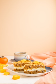 Domowe ciasto z persimmon i dynią oraz filiżankę kawy na białym i pomarańczowym tle z pomarańczową tkaniną. widok z boku, kopia przestrzeń.