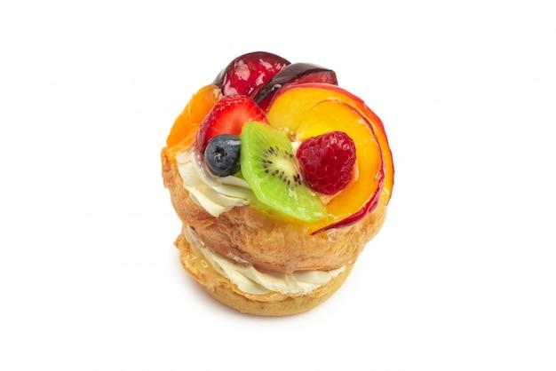 Domowe ciasto ze śmietaną i owocami na białym tle.
