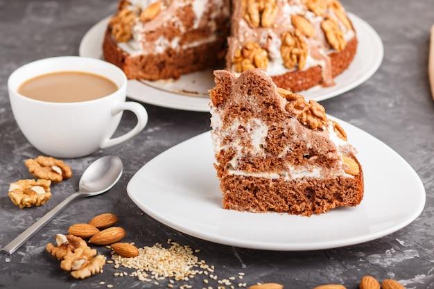 Domowe ciasto ze śmietaną mleczną, kakao, migdałami, orzechami laskowymi na czarnej betonowej powierzchni i filiżanką kawy. widok z boku.