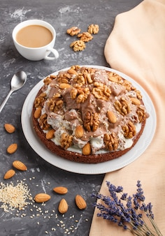 Domowe ciasto ze śmietaną mleczną, kakao, migdałami, orzechami laskowymi na czarnej betonowej powierzchni z pomarańczową tkaniną i filiżanką kawy. widok z boku.