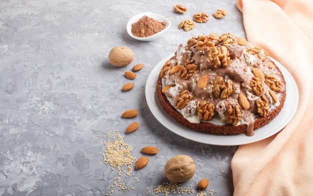 Domowe ciasto ze śmietaną mleczną, kakao, migdałami, orzechami laskowymi na szarym betonie z pomarańczową tkaniną, widok z boku.