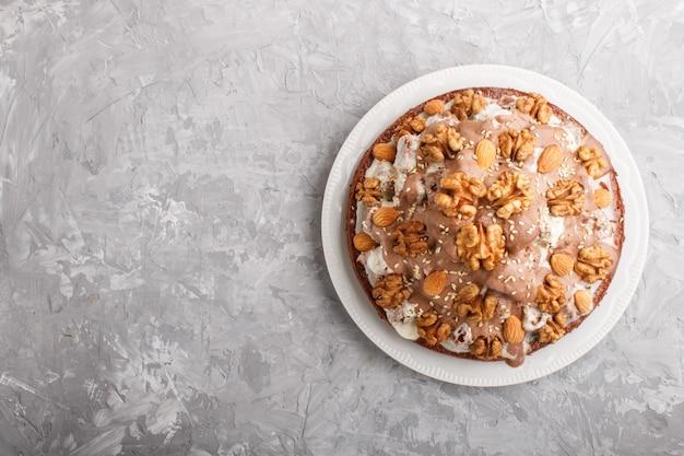 Domowe ciasto ze śmietaną mleczną, kakao, migdałami, orzechami laskowymi na szarym betonie z pomarańczową tkaniną. widok z góry, kopia przestrzeń.
