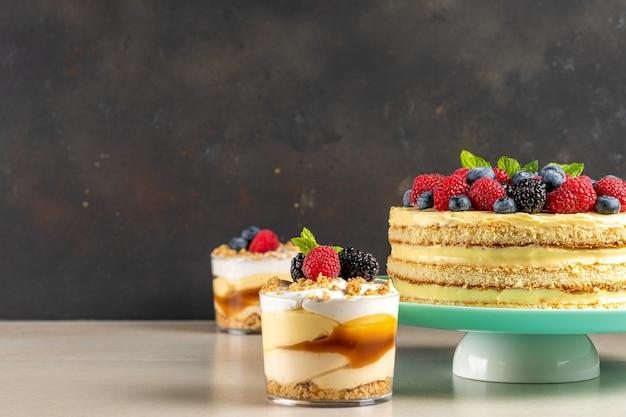 Domowe ciasto ze świeżymi jagodami i słodkimi deserami na ciemnej powierzchni.