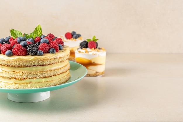 Domowe ciasto ze świeżymi jagodami i słodkimi deserami na stole.