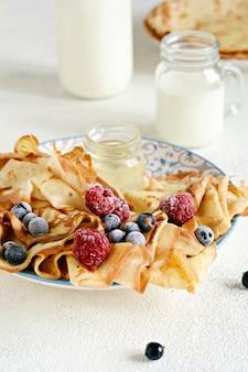 Domowe cienkie naleśniki z jagodami, miodem i mlekiem na śniadanie na jasnym tle tradycyjna kuchnia tydzień naleśników zapusty posiłek festiwalowy maslenitsa butter week
