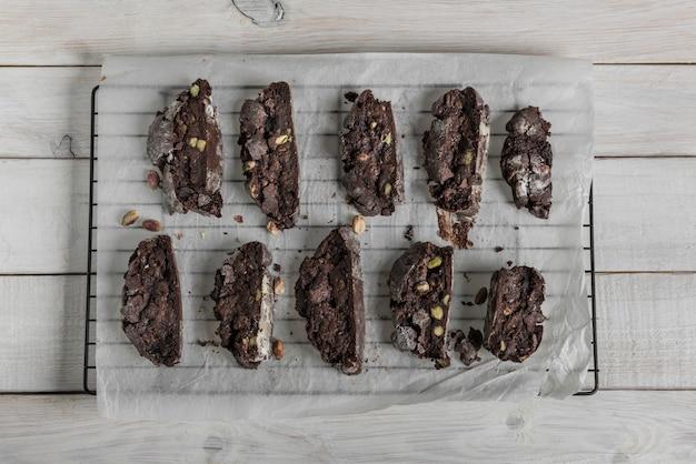 Domowe czekoladowe biscotti lub cantuccini z pistacjami na papierze do pieczenia na białym rustykalnym drewnianym stole.