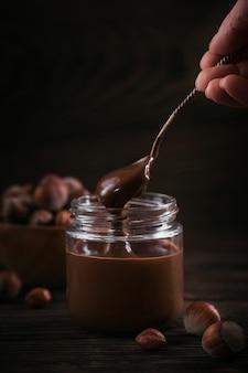 Domowe czekoladowe mleko z orzechów laskowych do smarowania na szklanym słoju na ciemnym drewnianym stole. ręka kobiety trzyma łyżkę