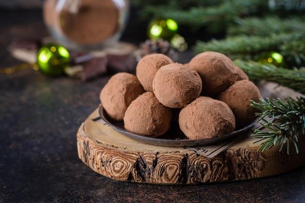 Domowe czekoladowe trufle na papierze na kamiennym betonowym stole z świąteczną dekoracją świąteczną. świąteczny deser