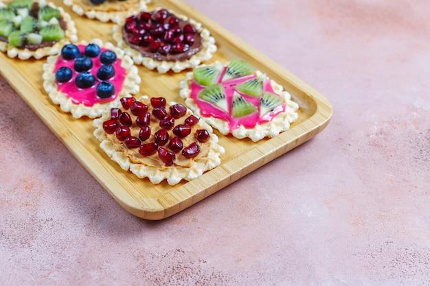 Domowe desery z jagodami, plasterkami kiwi i pestkami granatu.